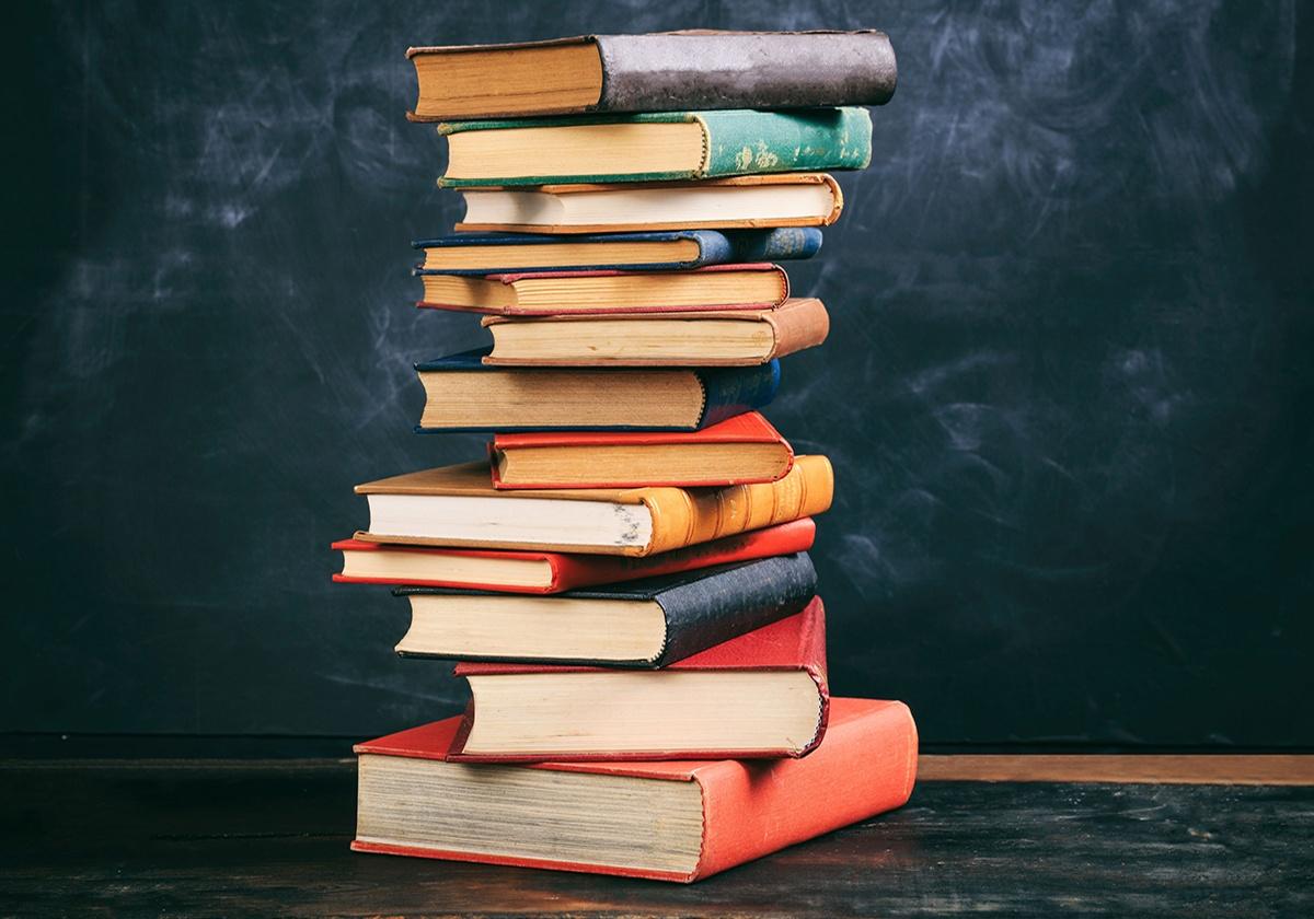 vintage books stack on blackboard background PTKNLJD0